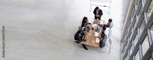 Poster Personal Top view of group of multiethnic busy people working in an office, Aerial view with businessman and businesswoman sitting around a conference table with blank copy space, Business meeting concept