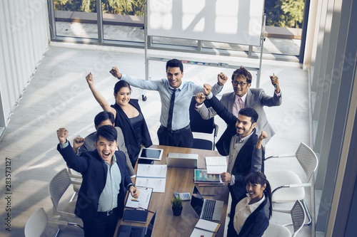 Photo  Successful startup entrepreneurs and business people team achieving goals celebrating a triumph with arms up in the office