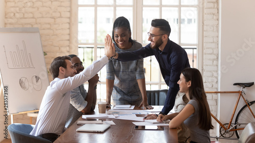 Cuadros en Lienzo  Motivated male colleagues give high five at multiracial group meeting