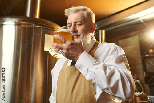 Poster de jardin Bar Man in shirt and apron standing in brewery and tasting beer
