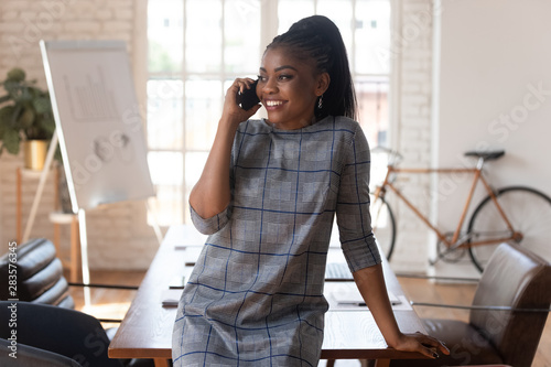 Fotografía Smiling black businesswoman talking on phone making call in office