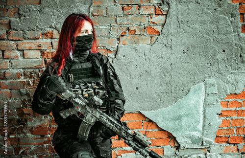 Fotografía  Airsoft red-hair woman in uniform with machine gun beside brick wall