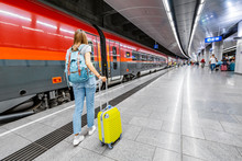 Traveler Woman With A Suitcase Walking To The Train At The Underground Station Platform In Airport