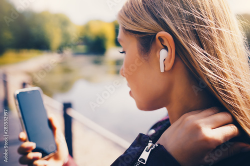 Fotografía  Young beautiful adult Caucasian girl walking outdoor in the park having chat com
