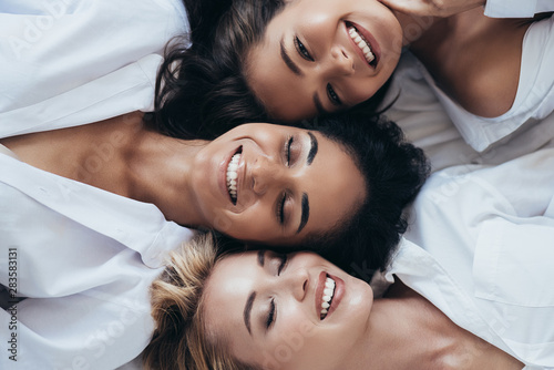 top view of three smiling multiethnic women in white shirts lying with closed ey Wallpaper Mural