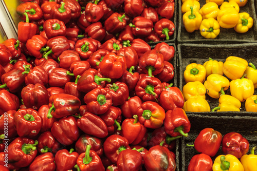 Fototapety, obrazy: Red and yellow peppers displayed in trays at a grocery store