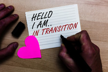 Handwriting Text Writing Hello I Am.. In Transition. Concept Meaning Changing Process Progressing Planning New Things Written On Notepad Hand Hold Marker With Love Heart Wooden Background