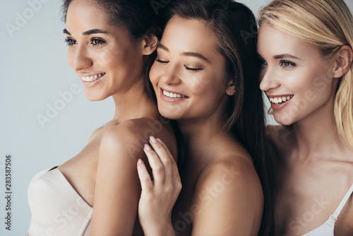 Carta da parati  three multiethnic smiling girls in underwear embracing isolated on grey