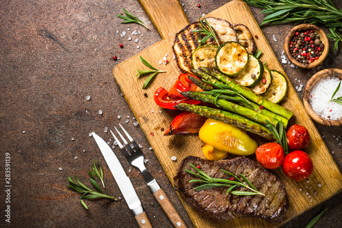 Pinturas sobre lienzo  Beef steak grilled with vegetables on cutting board