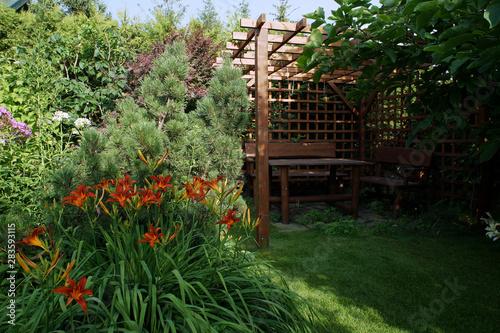 Altana i czerwone liliowce w lecie Fotobehang