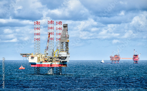 Oil rigs and supply vessels at sea