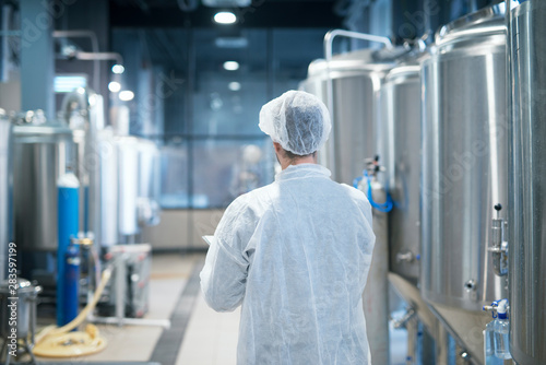 Technologist in white protective suit walking through food factory production line checking quality Wallpaper Mural
