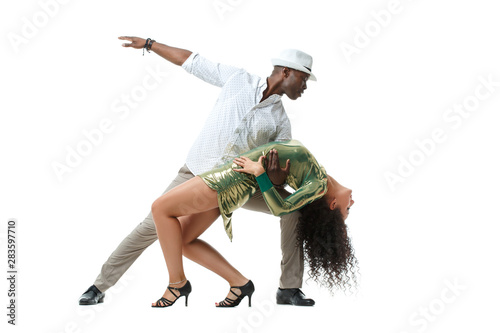 Fotografia, Obraz Beautiful white girl with magnificent curls and an elegant black man dancing in a pair of salsa, isolated on a white background