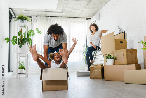 Fototapeta Happy playful  African American family moving in new apartment, little preschooler daughter sitting in cardboard boxes, father rolling her,  purchase property concept obraz