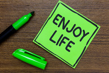 Conceptual Hand Writing Showing Enjoy Life. Business Photo Showcasing Any Thing, Place,food Or Person, That Makes You Relax And Happy Green Paper Communicate Ideas Marker Wooden Background