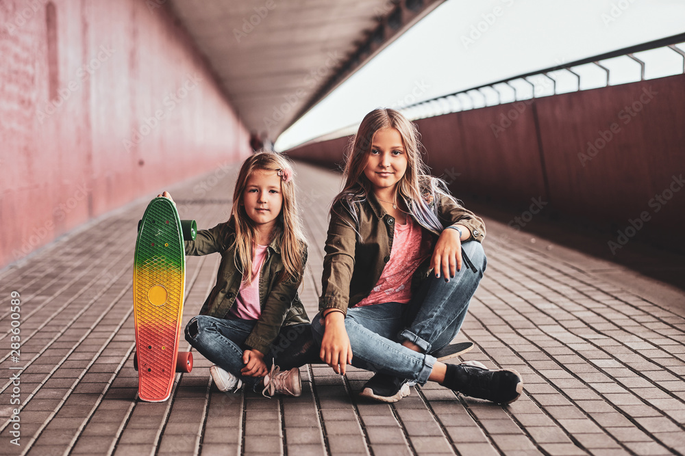 Fototapety, obrazy: Two little cheerful sisters are sitting on the skateboard in the tunnel.