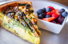 Vegetable Quiche Tart Portion Served With Fresh Fruits. Closeup View