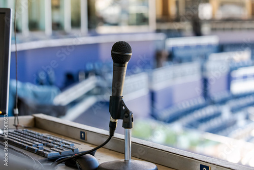 Photo Microphone resting in holder on desk of announcers booth for baseball stadium
