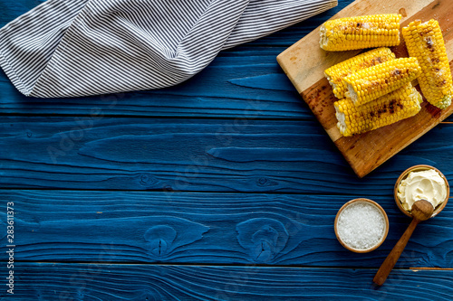Obraz na plátně Fried corn on board with salt and butter on blue wooden background top view mock