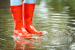 Leinwandbild Motiv Woman with red rubber boots in puddle, closeup. Rainy weather