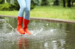 Leinwanddruck Bild - Woman with red rubber boots jumping in puddle, closeup. Rainy weather