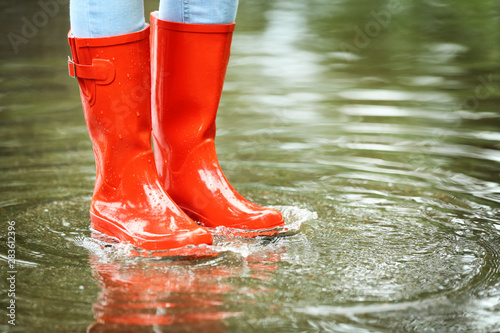 Foto auf Leinwand Texturen Woman with red rubber boots in puddle, closeup. Rainy weather
