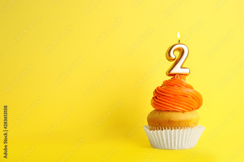 Fototapeta Birthday cupcake with number two candle on yellow background, space for text