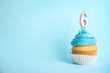 canvas print picture - Birthday cupcake with number six candle on blue background, space for text