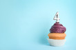 canvas print picture - Birthday cupcake with number four candle on blue background, space for text