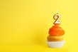 canvas print picture - Birthday cupcake with number two candle on yellow background, space for text