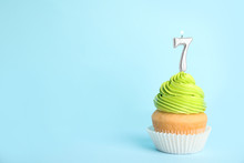Birthday Cupcake With Number Seven Candle On Blue Background, Space For Text