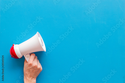 Fotografia, Obraz  Announcement with megaphone in hand on blue background top view mockup