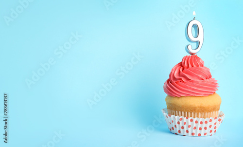 Birthday cupcake with number nine candle on blue background, space for text Wallpaper Mural
