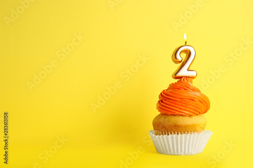 Birthday cupcake with number two candle on yellow background, space for text Canvas Print