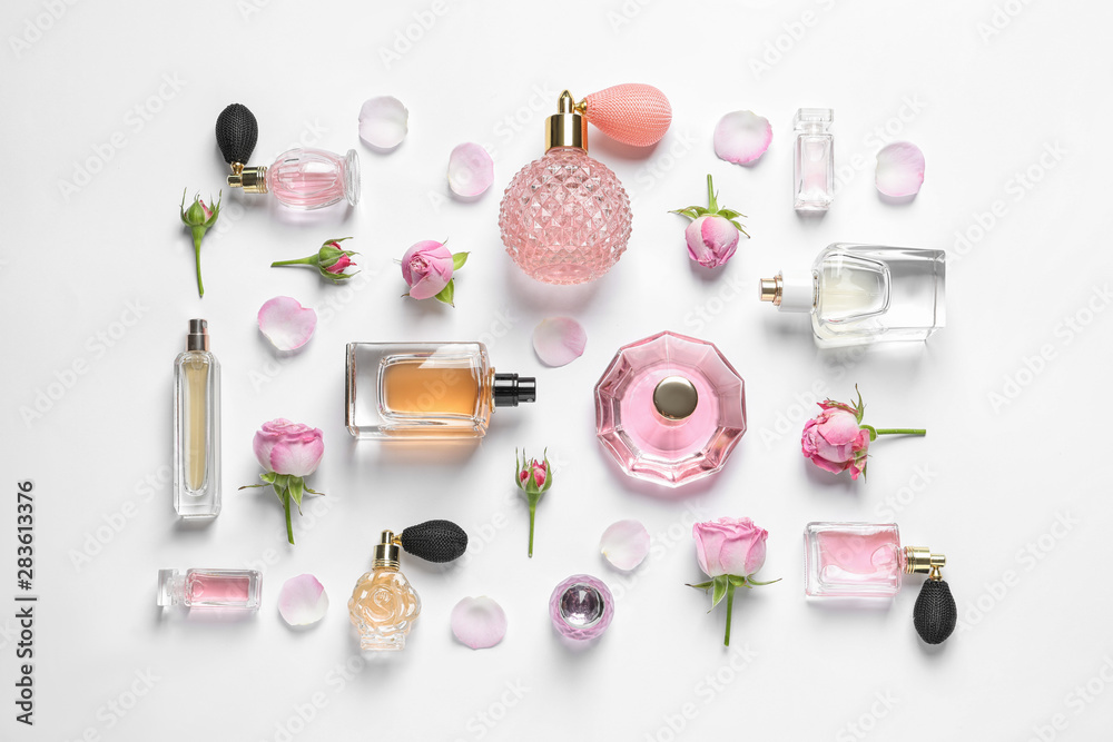 Fototapety, obrazy: Different perfume bottles and flowers on white background, top view