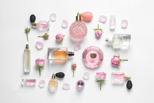 Different Perfume Bottles And Flowers On White Background, Top View