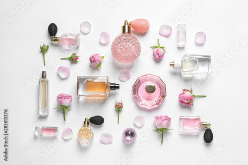 Fototapeta Different perfume bottles and flowers on white background, top view obraz
