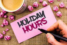 Conceptual Hand Writing Showing Holiday Hours. Business Photo Text Celebration Time Seasonal Midnight Sales Extra-Time Opening Written By Man Holding Marker Paper The Jute Background Cup