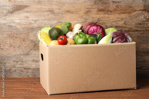 Fototapeta Fresh vegetables in cardboard box on wooden table obraz
