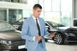 Young salesman with clipboard in modern car dealership