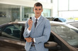 Young salesman with key near car in modern dealership