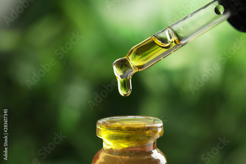 Leinwanddruck Bild - New Africa : Dripping essential oil from pipette into glass bottle against blurred green background, closeup