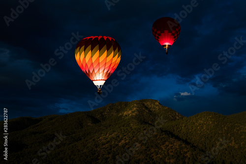 Poster Montgolfière / Dirigeable Colorful glowing hot air balloons floating in a night sky over forested mountain peaks