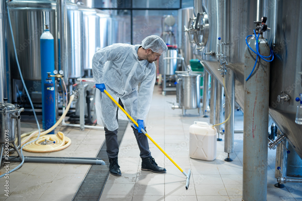Fototapeta Professional industrial cleaner in protective uniform cleaning floor of food processing plant. Cleaning services.
