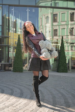 Pretty Woman Walking In The City With Grey Teddy Bear Of Foamirane Roses.