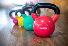 Colorful Kettlebells In A Row In A Gym, Red, Green, Yellow, Pink