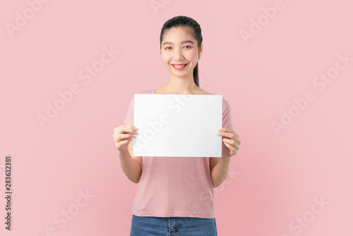 Obraz Young Asian woman holding blank paper with smiling face and looking on the blue background. for advertising signs. - fototapety do salonu