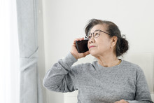 Asian Senior Woman Make A Phone Call White Sitting On Sofa At Home, Lifestyle Concept.