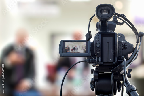 Obraz Video camera taking live video streaming at people talking with reporter background - fototapety do salonu