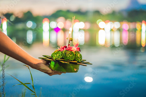 A female tourist holds the Loy Krathong in her hands and is about to launch it into the water Canvas Print